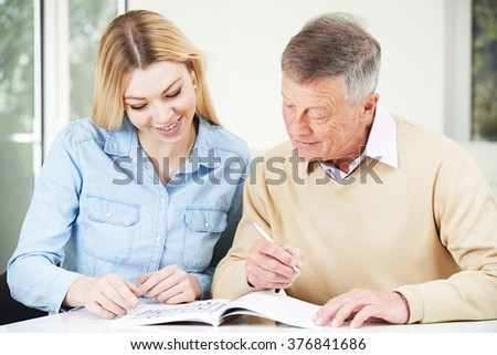 Senior Man Completing Crossword Puzzle With Teenage Granddaughter Daughter