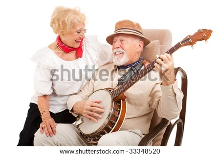 Senior man courts his lady love by playing banjo for her.  Isolated on white.