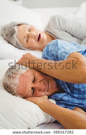 Senior man covering her ears while woman snoring in bed - stock photo