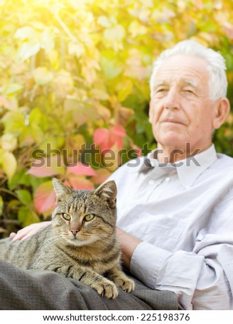 Senior man cuddle tabby cat in his lap in garden - stock photo