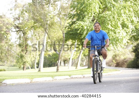 Senior Man Cycling In Park - stock photo