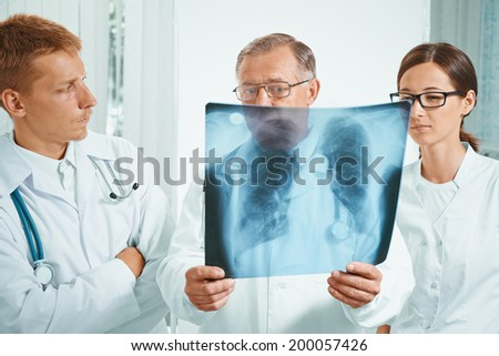 Senior man doctor and young doctors examine x-ray image of lungs in hospital - stock photo