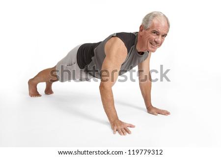 Senior man does push ups - stock photo