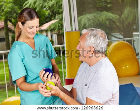 Senior man doing exercises with spikey balls at physiotherapy - stock photo