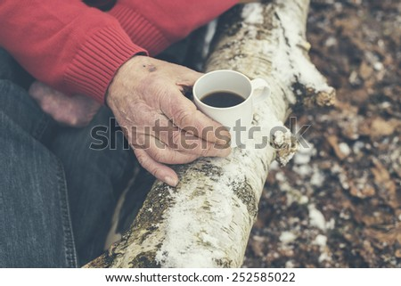Senior man drinking coffee in a winter forest resting his mug of black coffee on a tree trunk, close up of his hand - stock photo