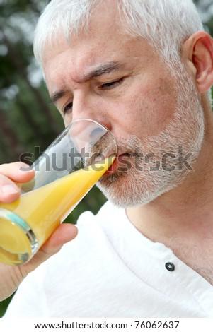 Senior man drinking orange juice - stock photo