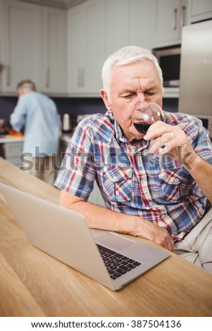 Senior man drinking red wine while using laptop and woman working in kitchen behind him - stock photo