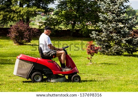 Senior man driving a red lawn mower (tractor) to the right and looking in front of himself - stock photo
