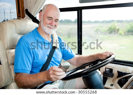 Senior man driving his motor home is using a GPS to navigate. - stock photo