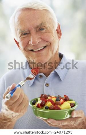 Senior Man Eating Fresh Fruit Salad - stock photo