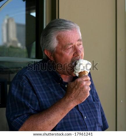 Senior man eating ice cream cone - stock photo
