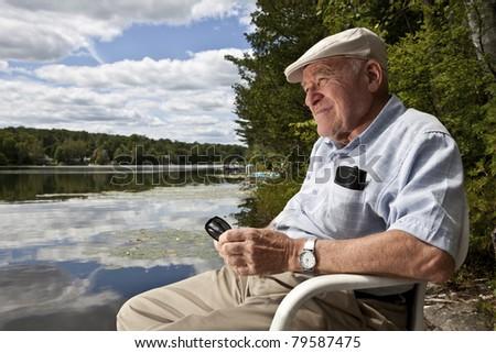 Senior man enjoying a day at the lake - stock photo