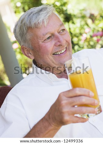 Senior man enjoying glass of juice sitting on garden seat - stock photo