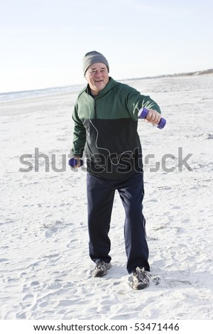 Senior man exercising with hand weights on beach listening to music - stock photo