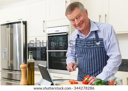 Senior Man Following Recipe On Digital Tablet - stock photo