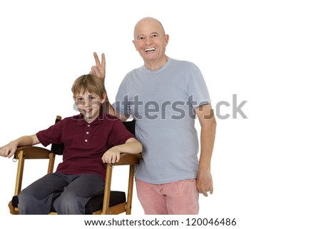 Senior man gesturing peace sign while preteen boy sitting on director's chair over white background - stock photo