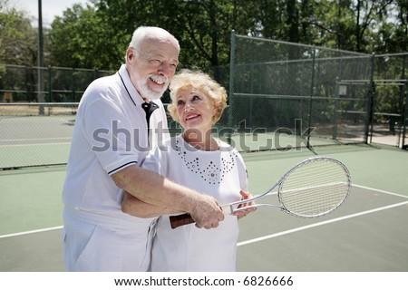 Senior man gives his wife pointers on tennis. - stock photo