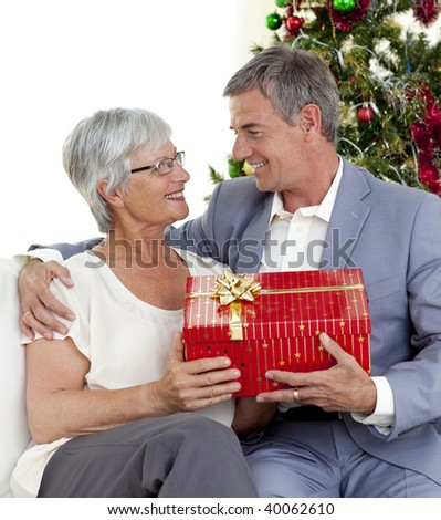 Senior man giving a Christmas present to his wife at home - stock photo