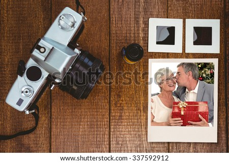 Senior man giving a kiss and a Christmas present to his wife against view of an old camera with photos slides - stock photo