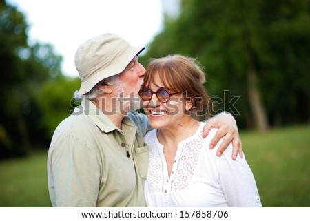 Senior man giving his wife a kiss on the cheek - stock photo