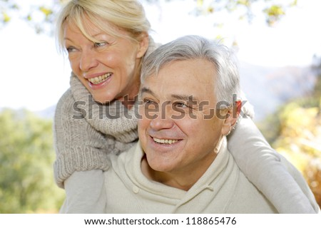 Senior man giving piggyback ride to wife - stock photo