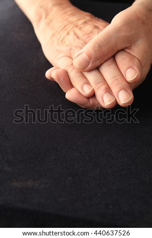 Senior man grasps his aching fingers, copy space included - stock photo