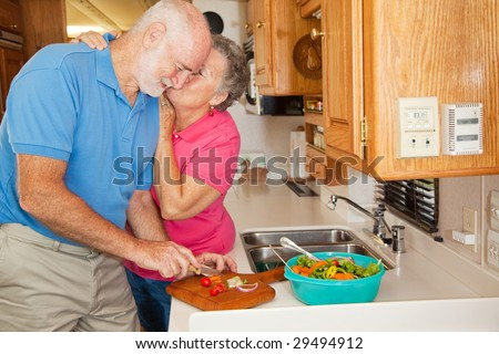 Senior man helping his wife in the kitchen of their RV gets rewarded with a kiss. - stock photo