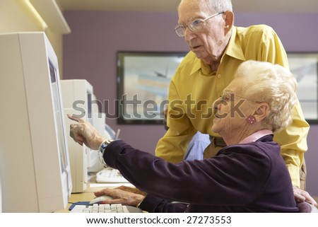 Senior man helping senior woman to use computer