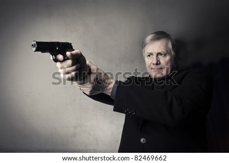 Senior man holding a gun - stock photo