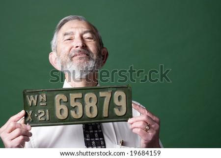Senior man holding antique license plate - stock photo