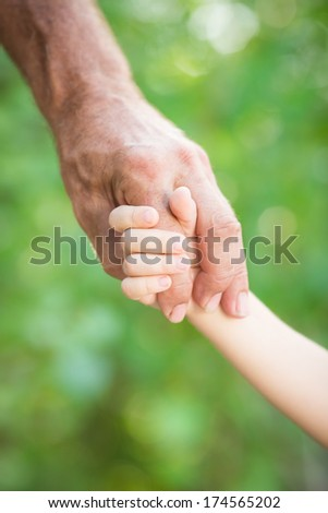 Senior man holding baby by the hands outdoors