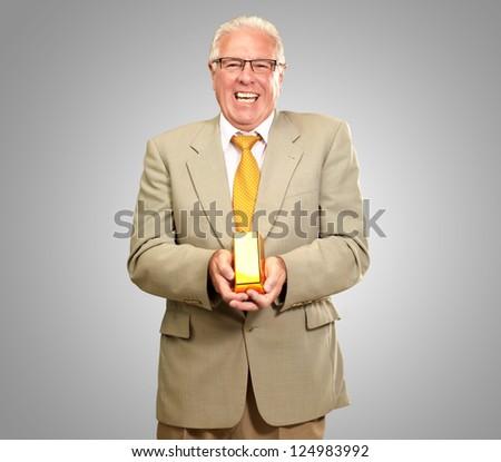 Senior Man Holding Gold Bar On gray Background - stock photo