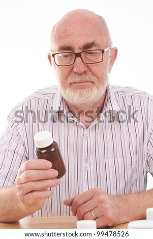 Senior man holding medicine bottles - stock photo