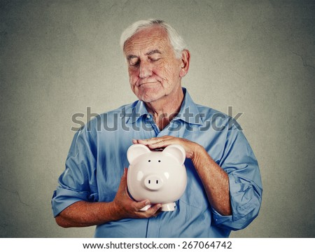 Senior man holding piggy bank isolated on gray wall background. Financial security planning concept