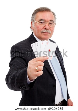 Senior man holding playing cards, showing all trumps, the four aces