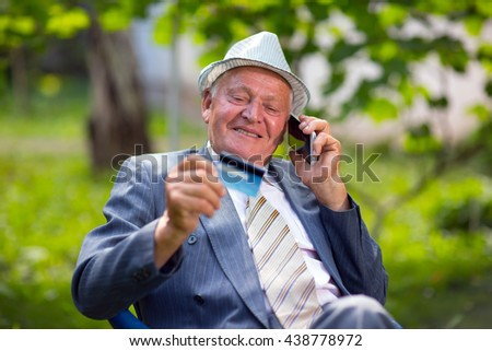 Senior man holds out a credit card cu laughs, using the phone - stock photo