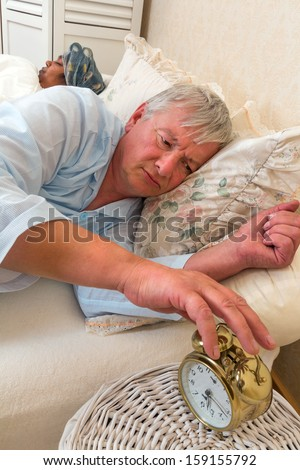 Senior man in bed with his wife early morning - stock photo
