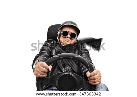 Senior man in black leather jacket and goggles driving very fast seated on a car seat isolated on white background