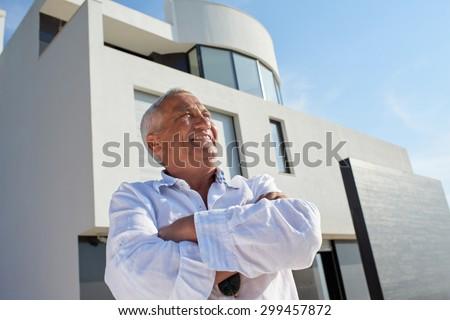 senior man in front of luxury modern home villa - stock photo