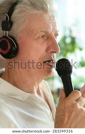 Senior man in headphones singing into microphone