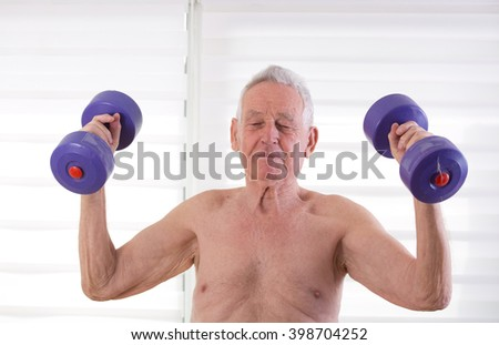 Senior man in his eighties training with dumbbells at home - stock photo
