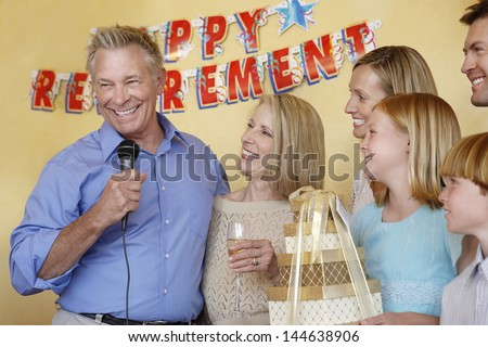 Senior man in his honor giving speech at retirement party with arms around wife by family - stock photo