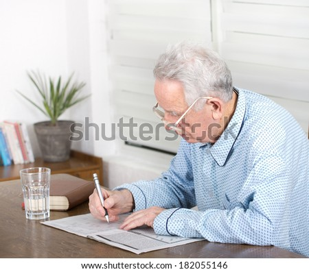 Senior man in pajamas with reading glasses sitting at table and solving crosswords - stock photo