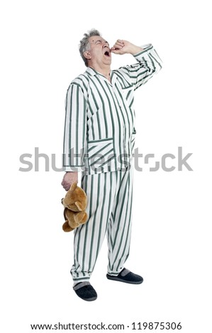 Senior man in pajamas with teddy bear isolated in white - stock photo
