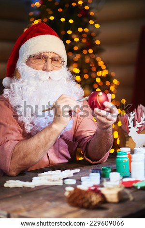 Senior man in Santa cap and beard painting toy ball and looking at camera - stock photo
