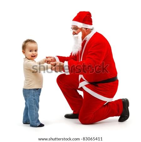 Senior man in Santa Claus uniform, holding hands of happy little boy - stock photo