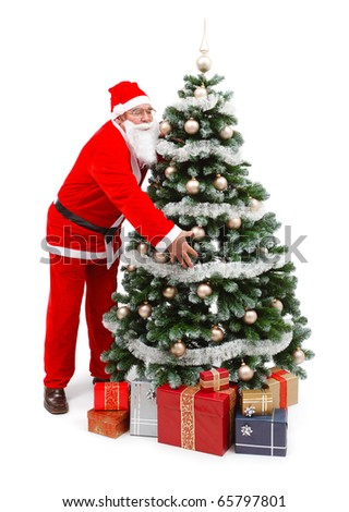 Senior man in Santa Claus uniform, taking the decorated Christmas tree, presents under the tree