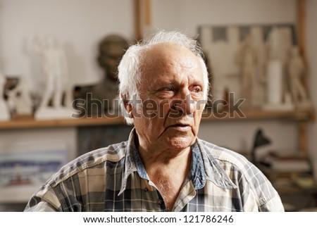 Senior man in sculptors workshop looking sideways - stock photo