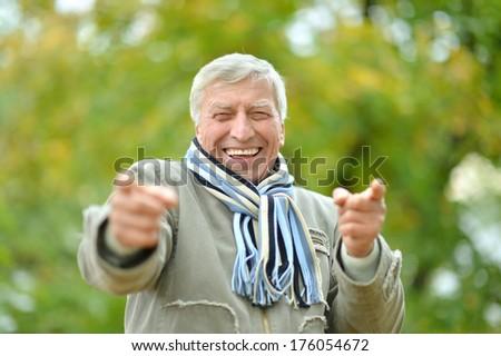 Senior man in the park in autumn - stock photo
