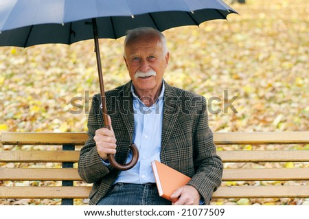 senior man in the park with umbrella - stock photo